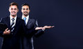 Two young businessman showing empty copyspace on black background Royalty Free Stock Photo