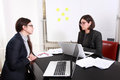 Two young businesswoman have a conversation at office Royalty Free Stock Images