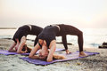 Two young caucasian females practicing yoga on beach Royalty Free Stock Photo
