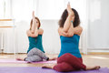 Two young caucasian woman doing gomukhasana with eagle arms Royalty Free Stock Photo