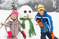 Two Young Children Building Snowman On Ski Holiday Stock Photos