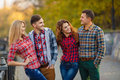 Two young couples spend time in the park boys and beautiful girls good friends all wear plaid shirts girls dressed blue jeans all Royalty Free Stock Images