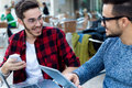 Two young entrepreneurs working at coffee shop. Royalty Free Stock Photo