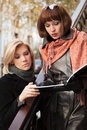 Two young fashion business women with a folder on city street Royalty Free Stock Photo