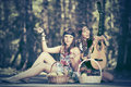 Two young fashion girls with fruit baskets in summer forest Royalty Free Stock Photo