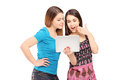 Two young female friends standing close together and looking at Stock Photos