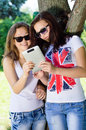 Two young female students with tablet pc outdoors teenage girs studens sitting in park Royalty Free Stock Images