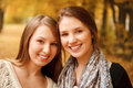 Two young females outdoors in autumn forest smiling looking at camera Stock Image