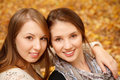 Two young females outdoors closeup of in autumn forest sitting looking at camera Stock Images