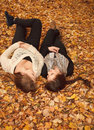 Two young females outdoors lying down in autumn forest Royalty Free Stock Images