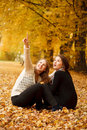 Two young females outdoors sitting in autumn forest Royalty Free Stock Photography