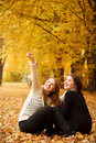 Two young females outdoors sitting in autumn forest Royalty Free Stock Images