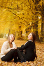 Two young females outdoors sitting on autumn leaves looking up Royalty Free Stock Image