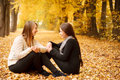 Two young females outdoors sitting talking in autumn forest smiling Stock Photography