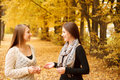 Two young females outdoors talking in autumn forest smiling Royalty Free Stock Photos