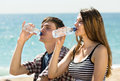 Two young friends drinking bottled water relaxing on the coast and Stock Photography