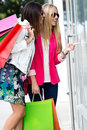 Two young friends shopping together happy in town Stock Photography