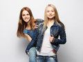 Two young girl friends standing together and having fun. Royalty Free Stock Photo