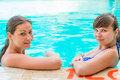 Two young girlfriends have a rest at the edge of the pool Stock Photo