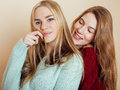 Two young girlfriends in winter sweaters indoors having fun. Lifestyle. Blond teen friends close up Royalty Free Stock Photo