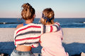 Two young girls, best friends sitting together on the beach at s Royalty Free Stock Photo