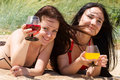 Two young girls drink cocktails at the beach Stock Photos