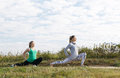 Two young girls exercising outdoors attractive athletic in the countryside doing stretching exercises to stay fit and tone their Stock Image