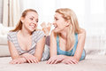 Two young girls on the floor friendship beautiful blond lying light looking at each other and smiling wearing pajamas Royalty Free Stock Photo