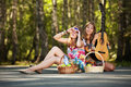 Two young girls with guitar in a summer forest hippie Stock Photo