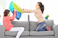 Two young girls having a pillow fight on sofa at home seated Royalty Free Stock Images