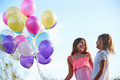 Two Young Girls Holding Bunch Of Colorful Balloons Outdoors Royalty Free Stock Photo