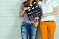 Two young girls holding a clapboard against brick wall with copy space Stock Photography