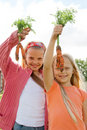 Two young girls  holding fresh carrots Stock Image