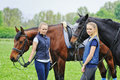 Two young girls  with horses Royalty Free Stock Photo