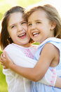Two Young Girls Hugging In Summer Field Royalty Free Stock Image