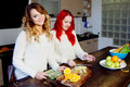 Two young girls in the kitchen talking and eating fruit, healthy lifestyle Royalty Free Stock Photo