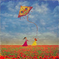 Two young girls with the kite on the field of poppies Royalty Free Stock Photo