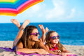 Two young girls laying together on beach. Royalty Free Stock Photo
