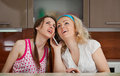Two young girls make a phone call on the kitchen Stock Photo
