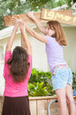 Two young girls painting a lemonade stand sign working together to paint hand print on Royalty Free Stock Photos