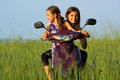 Two young girls playing outdoor on scooter Royalty Free Stock Image