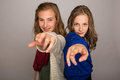 Two young girls pointing their fingers at camera kids the Stock Photo