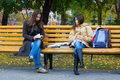 Two young girls reading in the park. Stock Images