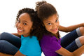Two young girls sitting together african descent teenagers back to back isolated on white background Royalty Free Stock Photos
