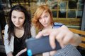 Two young girls taking a self portrait selfie with smart phone Stock Photography