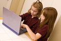 Two young girls working laptop computer one young watches as other girl points out something keyboard screen minimal selective Stock Photography
