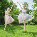 Two young happy beautiful women fashion in ballet dress jumping on green grass Stock Images