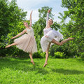 Two young happy beautiful women fashion in ballet dress jumping on green grass Stock Photos