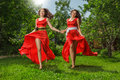Two young happy beautiful women fashion in long red dress running on green grass Royalty Free Stock Photography