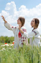Two young happy girls in traditional ukrainian dress in wheat field Royalty Free Stock Photo